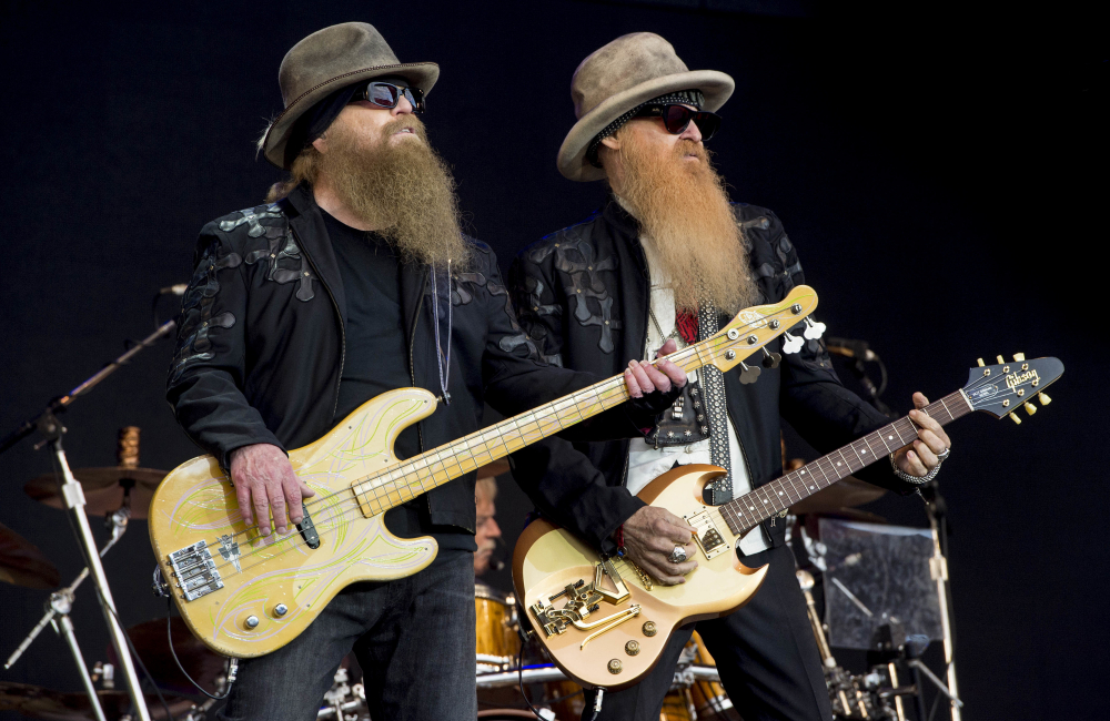 Dusty Hill, left, and Billy Gibbons from the rock band ZZ Top perform at the Glastonbury music festival in Somerset, England, in 2016. ZZ Top has announced that Hill, one of the Texas blues trio's bearded figures and bassist, has died at his Houston home. He was 72.