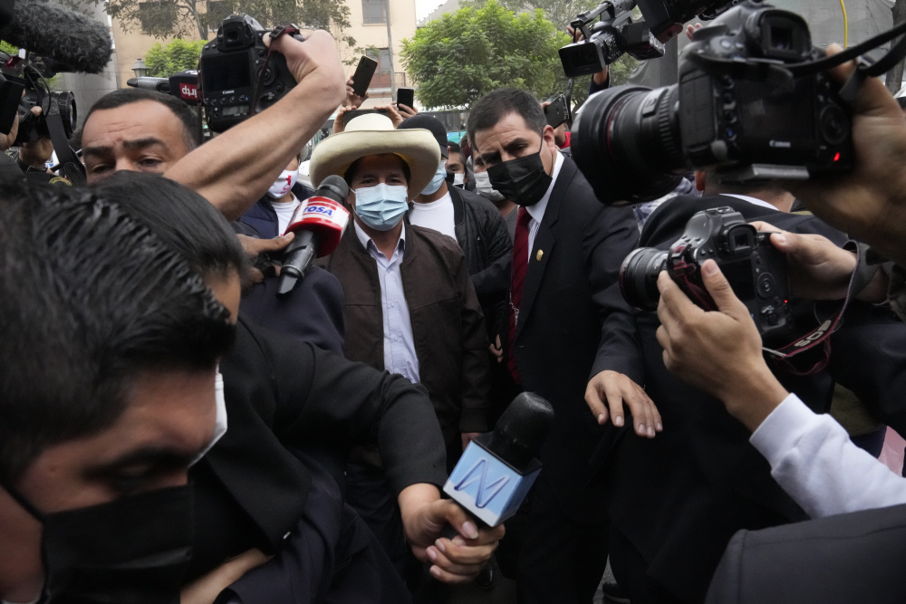 Pedro Castillo is surrounded by journalists June 15 as he arrives at his campaign headquarters t in Lima, Peru.