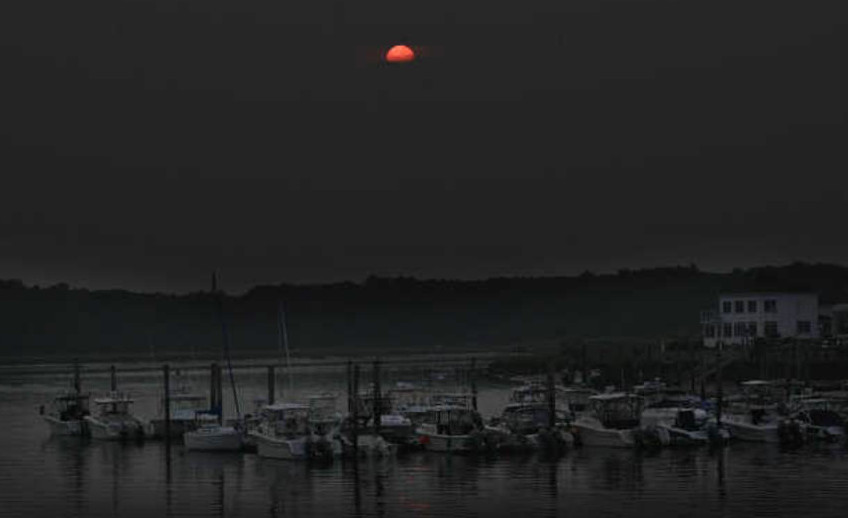 A hazy sun sets over the Saco River in Camp Ellis on Monday. State officials are recommending that people with respiratory conditions avoid strenuous outdoor activity through Tuesday because of unhealthy air quality caused by western wildfires.