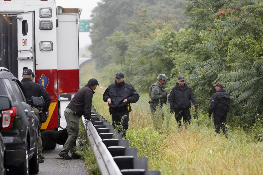 Police work in the area of an hours long standoff with a group of armed men that partially shut down interstate 95 on Saturday in Wakefield, Mass.