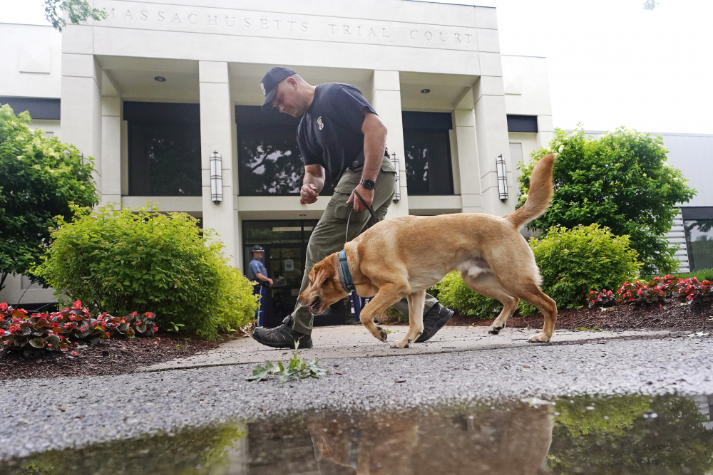 A Massachusetts State Police K-9 team searches for explosives outside Malden District Court, Tuesday, July 6, in Medford, Mass. The men arrested during an armed standoff on Interstate 95 in Massachusetts last weekend appeared in court.