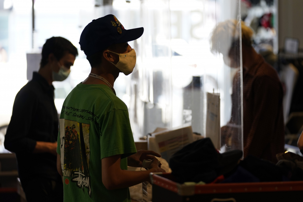 Employees check out customers at 2nd Street second hand store in the Fairfax district of Los Angeles on July 19.  New evidence showing the delta variant is as contagious as chickenpox has prompted U.S. health officials to consider changing advice on how the nation fights the coronavirus.