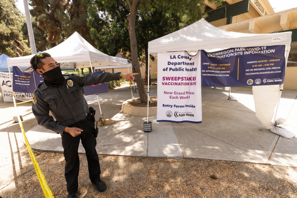 A private security guard gives directions to people looking to get vaccinated, as banners advertise the availability of the Johnson & Johnson and Pfizer COVID-19 vaccines at a county-run vaccination site offering free walk-in vaccinations with no appointment needed at the Eugene A. Obregon Park in Los Angeles on Thursday.