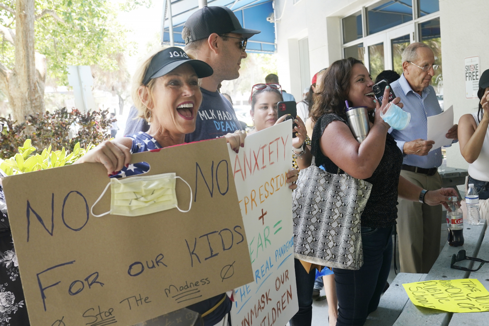 Joann Marcus of Fort Lauderdale, left, cheers as she listens to the Broward School Board's emergency meeting  Wednesday in Fort Lauderdale, Fla. A small but vocal group spoke vehemently against masks, saying their personal rights were being eroded and their children were suffering socially.