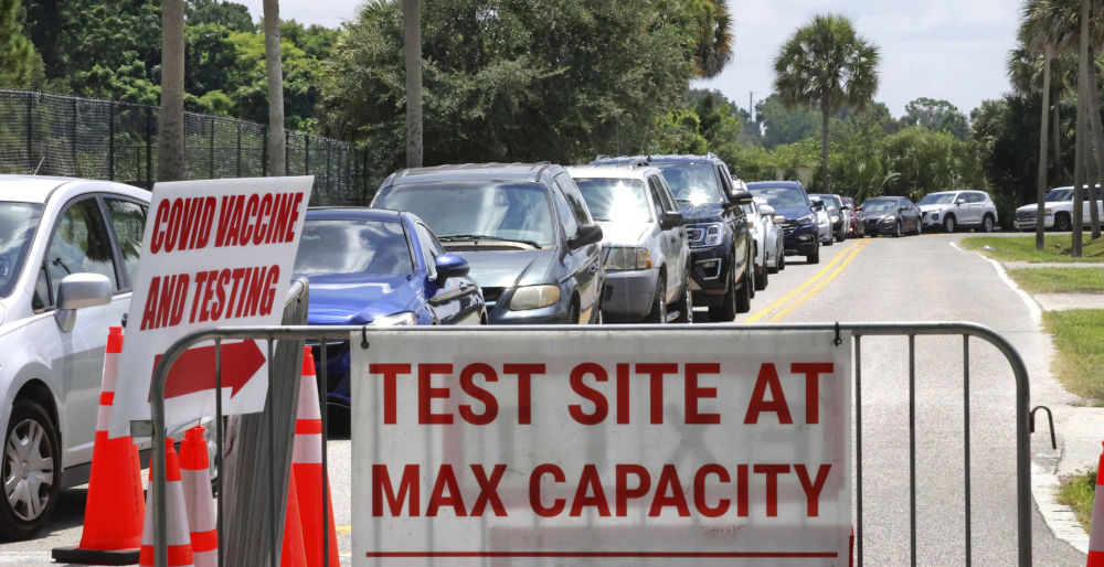 Signage stands at the ready in case COVID-19 testing at Barnett Park reaches capacity, as cars wait in line in Orlando, Fla., on Thursday.