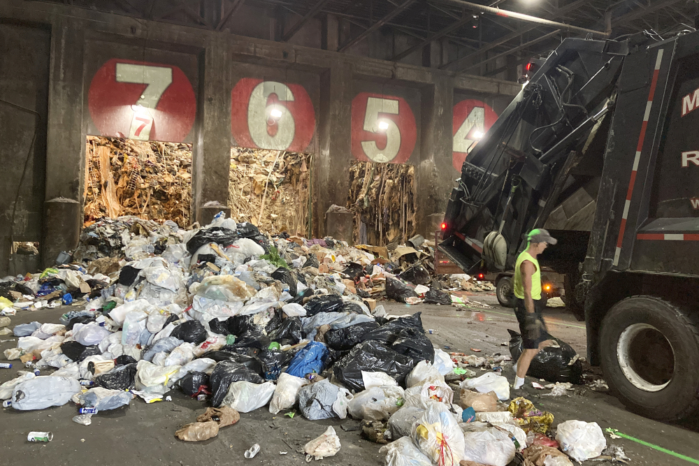 A worker unloads a garbage truck at ecomaine in Portland in June.