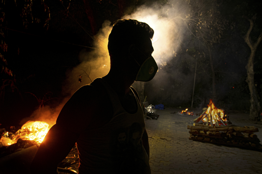 Ramananda Sarkar, 43, who had cremated more than 450 COVID-19 victims, stands by burning funeral pyres of COVID-19 victims in Gauhati, India, in September.