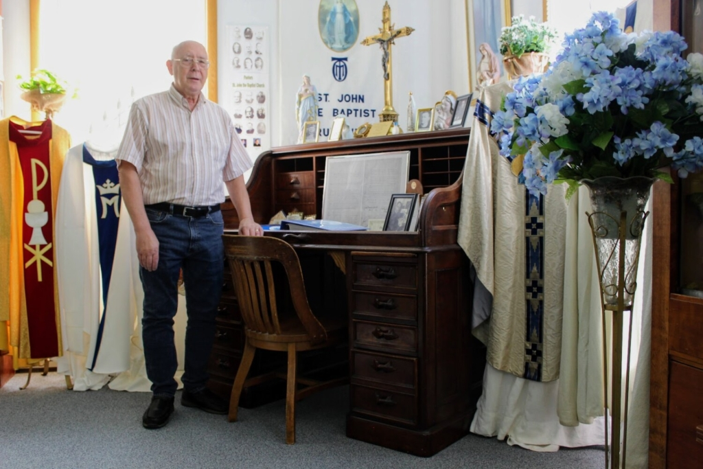 Church Historian Robert Bouchard standing next to the pastor's desk that he believes is one of the oldest artifacts in the museum.