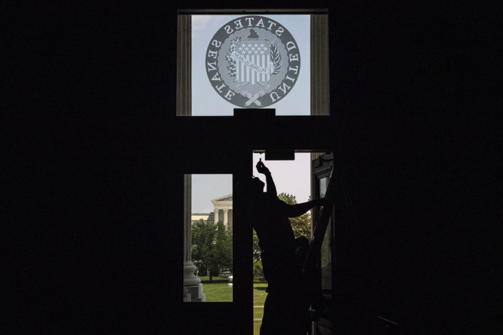 A worker fixes a door at the U.S. Capitol in May. Democrats have only a matter of weeks to settle many of the biggest policy questions surrounding a bill that could transform much of American life and they'll be voting with some of the thinnest margins Capitol Hill has even seen, with a 50-50 Senate majority secured by Vice President Kamala Harris's tiebreaking vote, and a four-seat margin in the House.