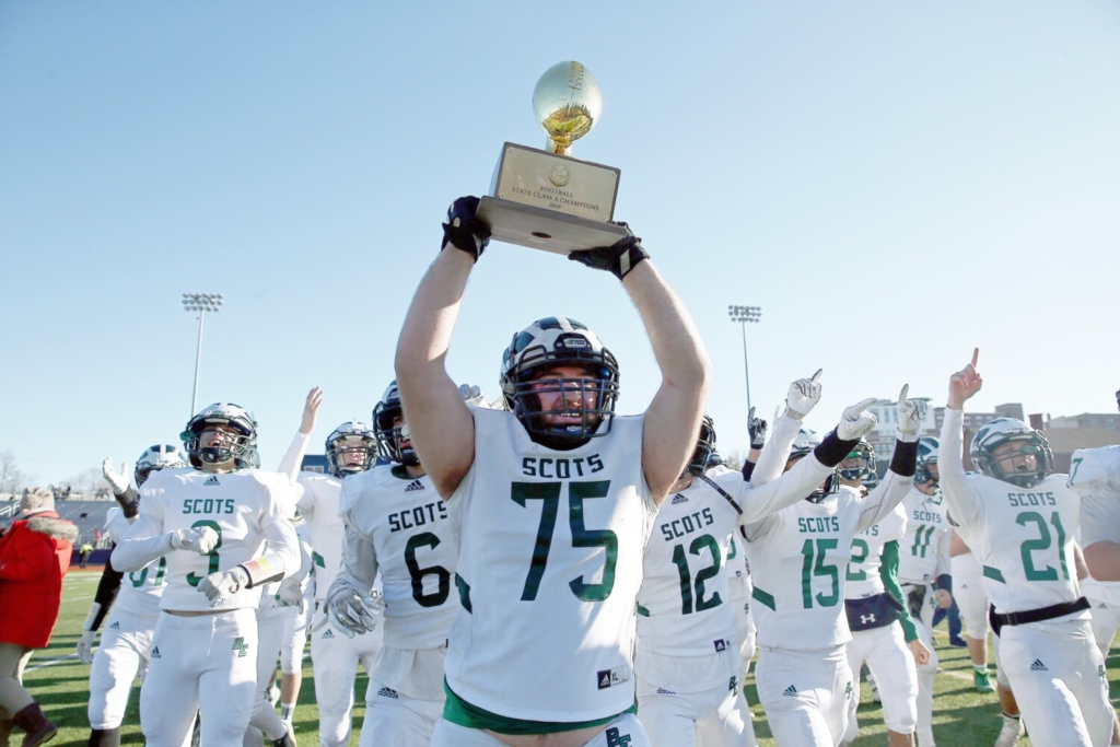 PORTLAND, ME - NOVEMBER 23: Bonny Eagle's Will Horton is surrounded by teammates as he holds the trophy ball up for the crowd in the stands after winning the Class A football state championship game against Thornton Academy on Saturday at Fitzpatrick Stadium. (Staff photo by Ben McCanna/Staff Photographer)