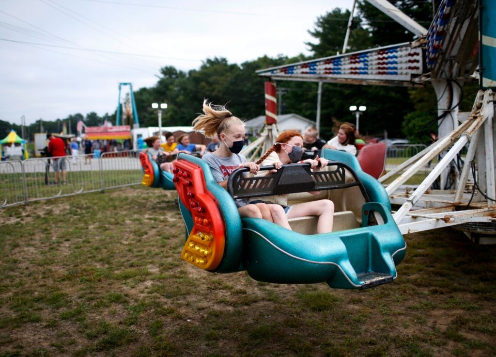 Isabel Chabot, 11, left, and Lyra Ricciardone, 11, both of Bath, spin around on a ride at the Topsham Fair on Tuesday.