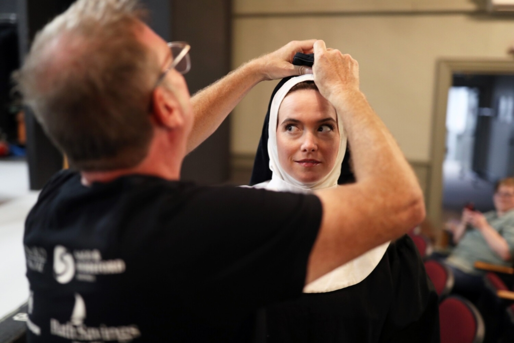 """Director Joshua Chard adjusts Molly Frantzen's habit before a rehearsal of the one-person show """"Sister Robert Anne's Cabaret Class,"""" part of the Nunsense franchise, at Lyric Music Theater in South Portland."""