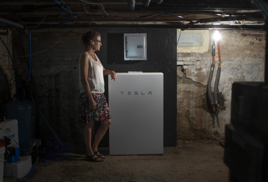 Julie Isbill stands next to the Tesla Powerwall battery backup system she had installed in the basement of her home in Brunswick on Aug. 13. Experts say residences will need to adapt their homes to accommodate higher temperatures and more extreme weather events.