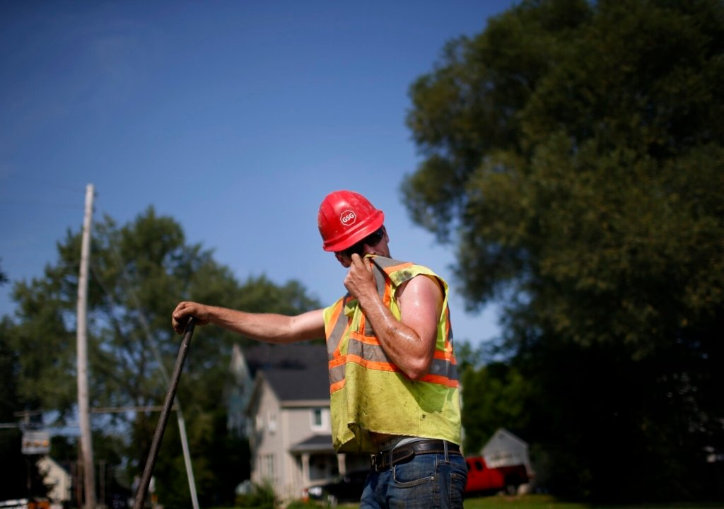 PORTLAND, ME - AUGUST 12: Cody Kinney of Gorham Sand and Gravel wipes sweat from his face while working on Ocean Avenue in Portland on Thursday, Aug. 12, 2021. (Staff photo by Derek Davis/Staff Photographer)