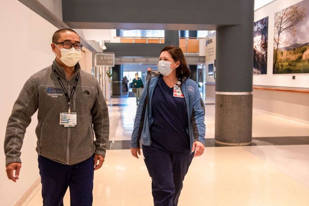 Dr. Al Teng, Chief of Critical Care, and Jennifer Jordan, the System Director of Medical Specialties walk together on Friday in the hallway of Central Maine Medical Center in Lewiston. Jordan oversees the hospital's mass vaccination program at the Auburn Mall.