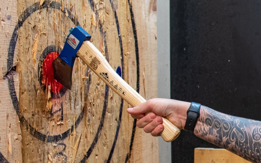 Christina Tucci pulls her axe from the bullseye that she just hit with one of her throws Thursday night at Splittin' Wood Axe Throwing at the Lewiston Mall.