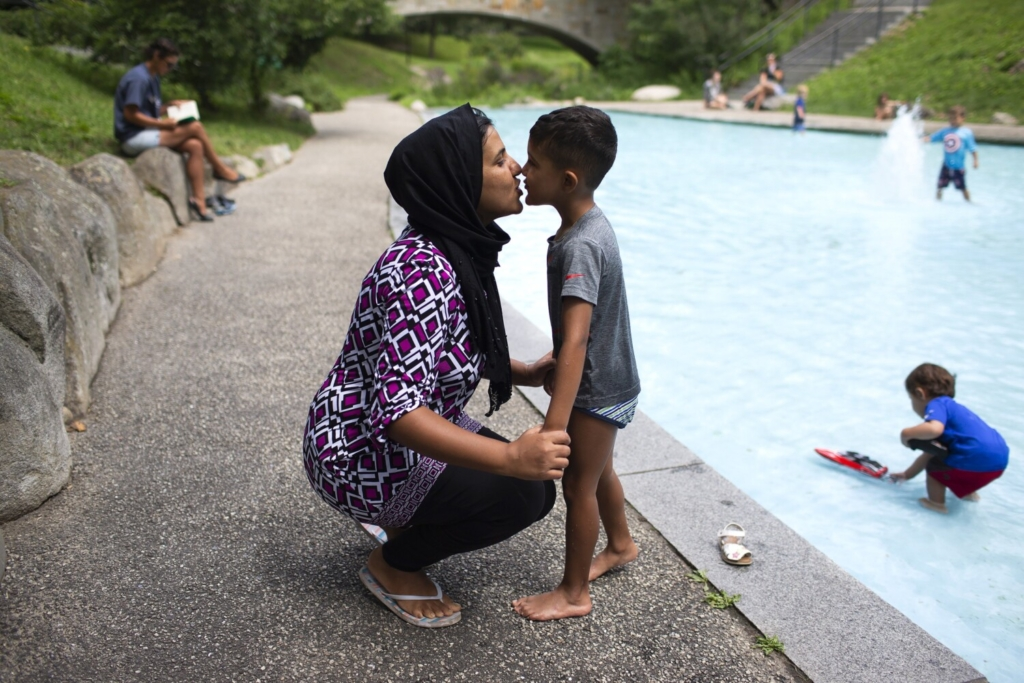 Sameera Khilwati kisses her son, Rustam Jamalzada, 5, as he takes a break from playing at Deering Oaks on Wednesday. With Rustam going into kindergarten at Rowe Elementary School in Portland, she is worried about COVID-19 and thinks it would be good if schools reopened online.