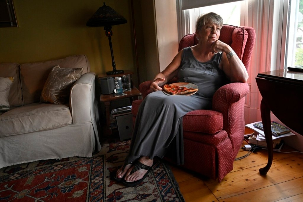 PORTLAND, ME - AUGUST 25: After having a few bites at the kitchen counter Diane moved to the living room to enjoy her pizza Wednesday, August 25, 2021. Diane said she use to hate pizza but now she likes it. (Staff Photo by Shawn Patrick Ouellette/Staff Photographer)