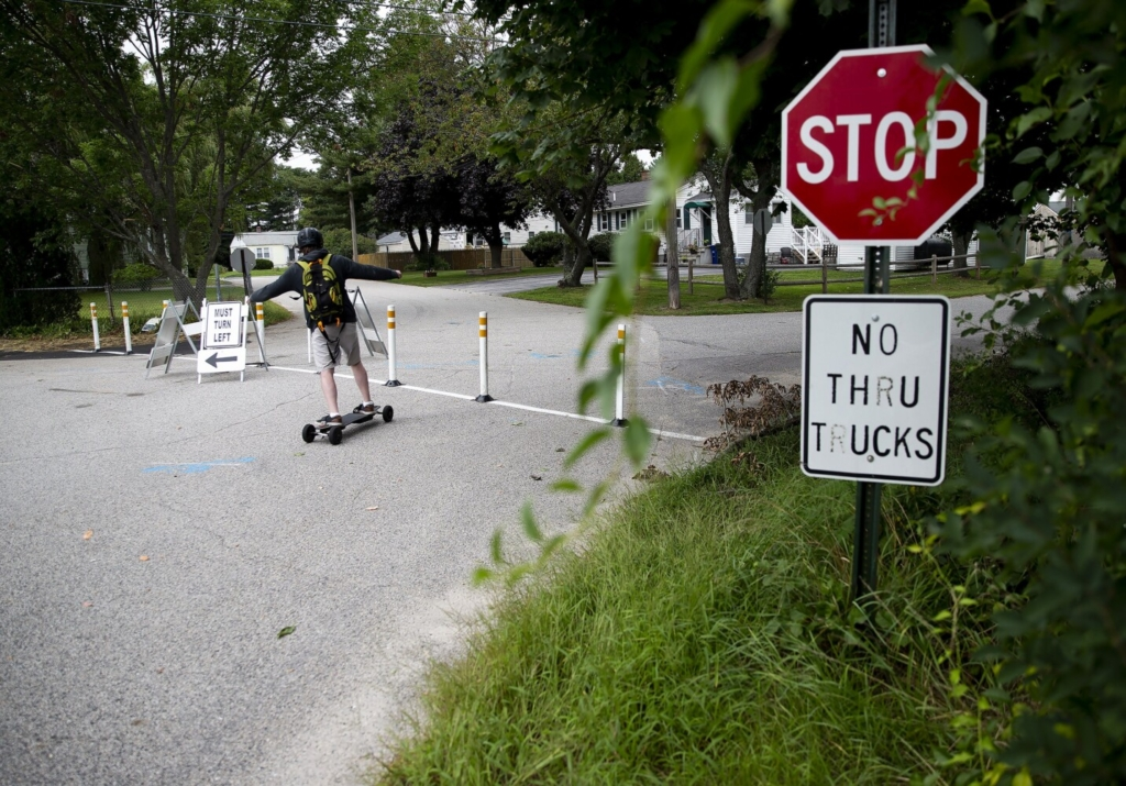 SOUTH PORTLAND, ME - AUGUST 21: A boy skateboards past temporary signs directing traffic away from a residential neighborhood in the Cash Corner neighborhood in South Portland. The City of South Portland and the Greater Portland Council of Governments installed several traffic calming treatments in order to analyze existing conditions and develop a report on traffic calming implementations. These installations will be in place for a trial period of two months, with removal anticipated for early October. (Davis/Staff Photographer)