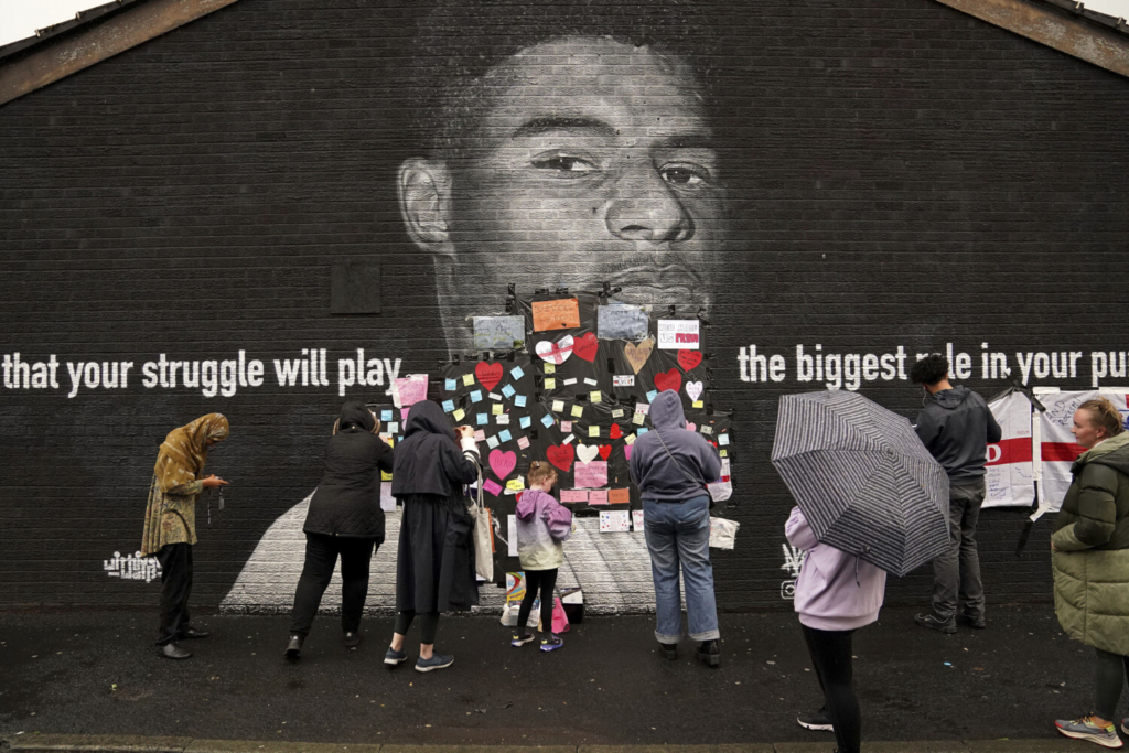 People place messages of support on top of bin liners that were taped over offensive wording on the mural of Manchester United striker and England player Marcus Rashford on the wall of the Coffee House Cafe on Copson Street, which appeared vandalised the morning after the England soccer team lost the Euro 2021 final against Italy, in Withington, Manchester, England, Monday,  July 12, 2021.