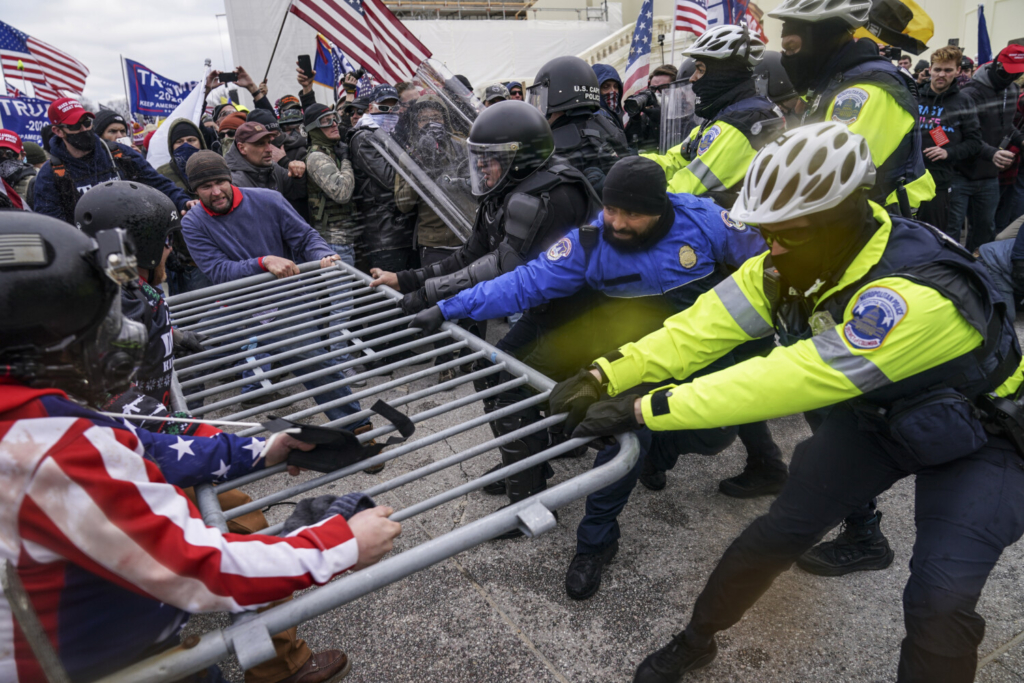 Violent insurrectionists loyal to President Donald Trump hold on to a police barrier at the Capitol in Washington on Jan. 6.