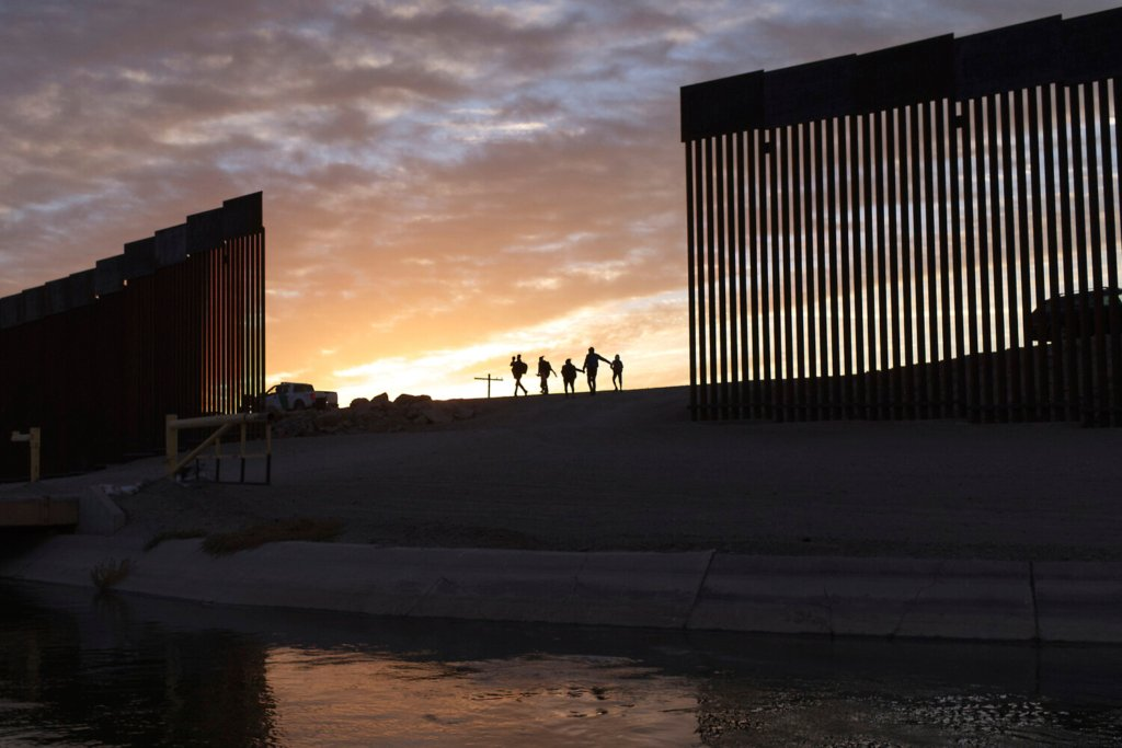 A pair of migrant families from Brazil pass through a gap in the border wall to reach the United States after crossing from Mexico to Yuma, Ariz., to seek asylum on June 10.  More than 55,800 family members arrived at the border in June.