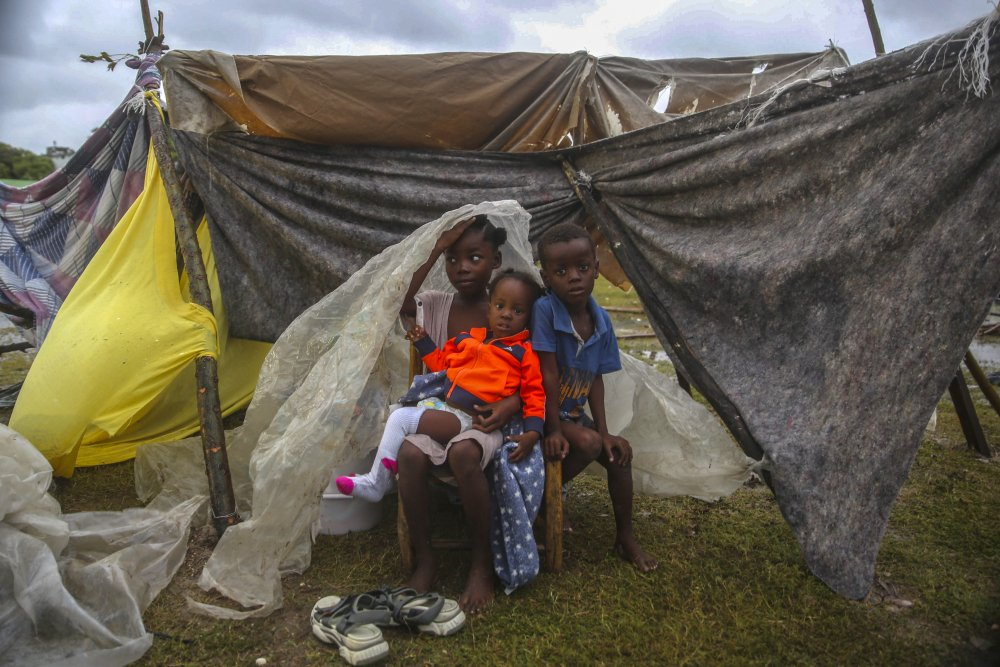 Children displaced by the earthquake huddle under a piece of plastic the morning after Tropical Storm Grace swept over Les Cayes, Haiti, on Tuesday, three days after a 7.2-magnitude earthquake.