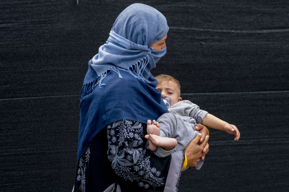 A woman evacuated from Afghanistan steps off a bus with a baby as they arrive at a processing center in Chantilly, Virginia, on Monday after arriving on a flight at Dulles International Airport.
