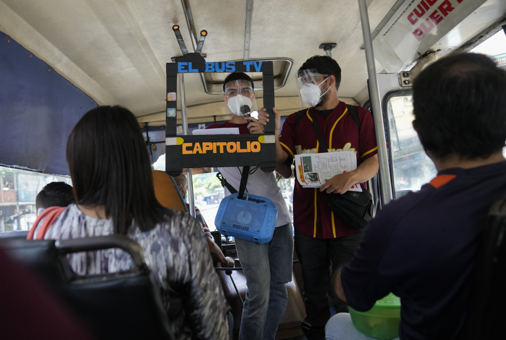"""Juan Pablo Lares, right, holds a cardboard frame in front of his associate Maximiliano Bruzual who reads their newscast """"El Bus TV Capitolio"""" to commuters on a bus in Caracas, Venezuela. (AP Photo/Ariana Cubillos)"""