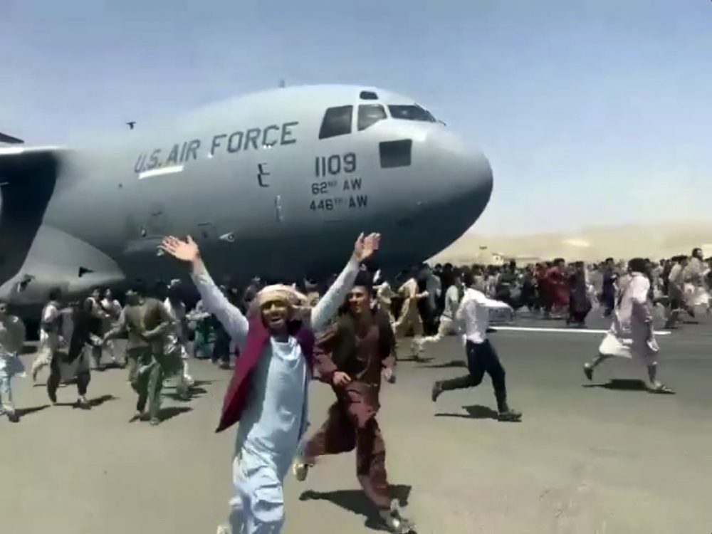 Hundreds of people run alongside a U.S. Air Force C-17 transport plane as it moves down a runway  of the international airport in Kabul, Afghanistan, on Monday. Thousands of Afghans have rushed onto the tarmac of Kabul's international airport in a desperate attempt to escape the Taliban capture of their country.