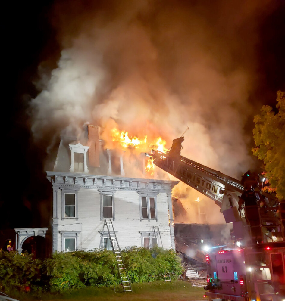 Lewiston Fire Department ladder truck works on one of the sides of a fire at 63 Academy St. in Auburn in 2018.