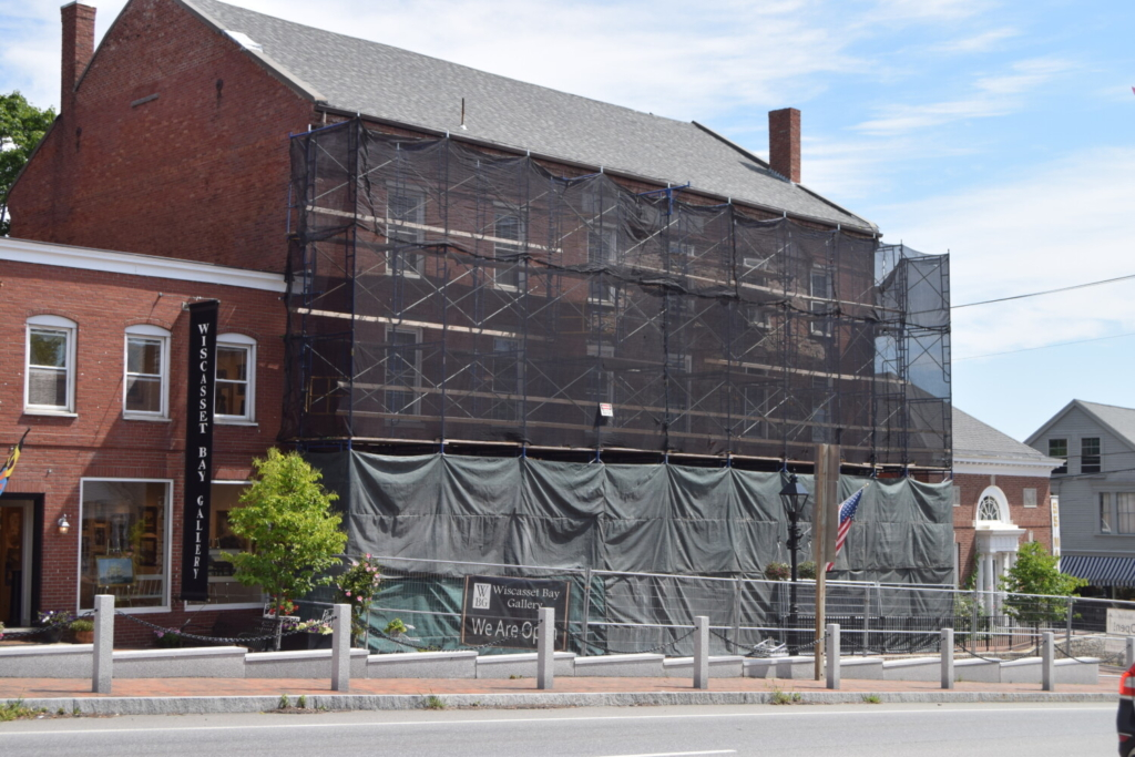 The front of the Wawenock Block building in downtown Wiscasset is covered in scaffolding to stabilize it and prevent more bricks from falling off. The building owner still doesn't know when repairs on the building will begin.
