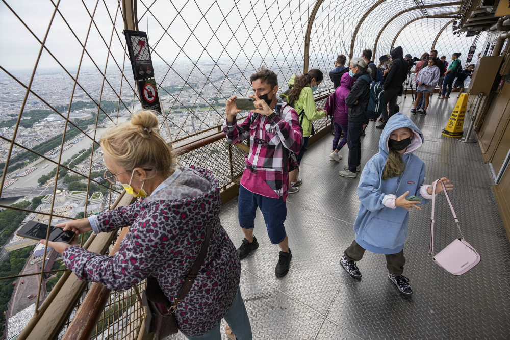 Visitors enjoy the view from top of the Eiffel Tower in Paris on July 16.