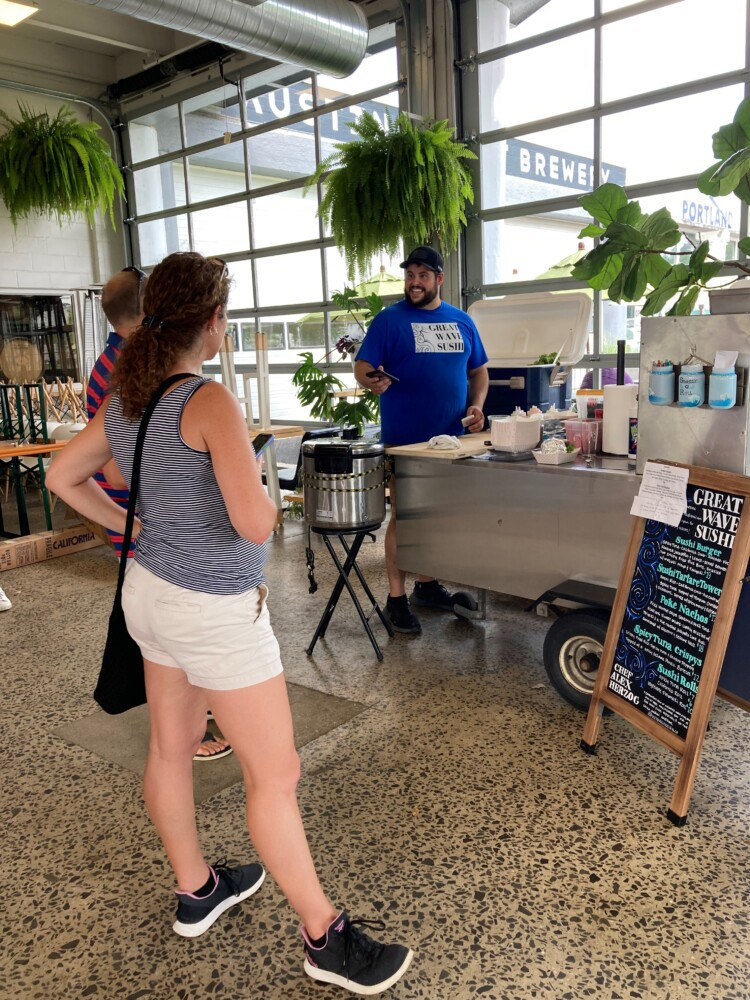 Alex Herzog, chef and founder of the Great Wave Sushi cart, chats with a customer inside the Austin Street Brewery in Portland on a July afternoon.