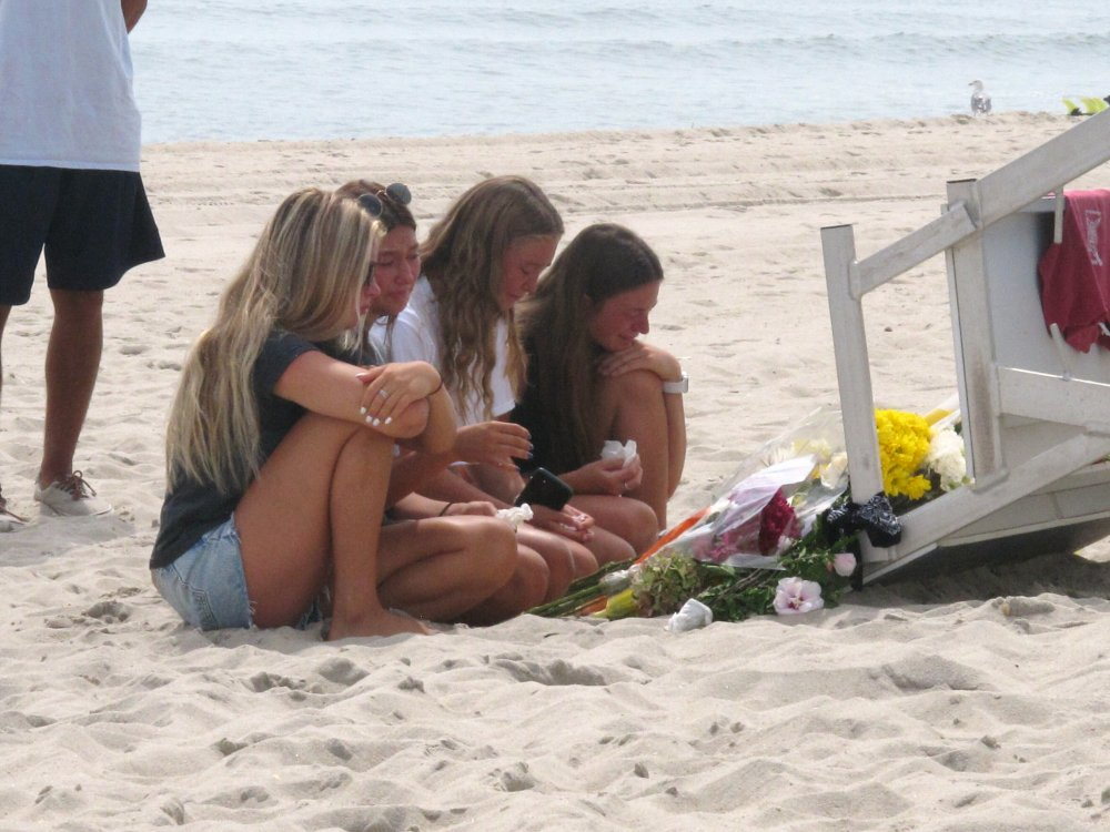 Friends and fellow lifeguards cry at the foot of a lifeguard stand in Berkeley Township, N.J., on Tuesday, a day after 19-year-old lifeguard Keith Pinto was killed by lightning there. Pinto, of Toms River, was among eight people who were hit by lightning Monday afternoon.