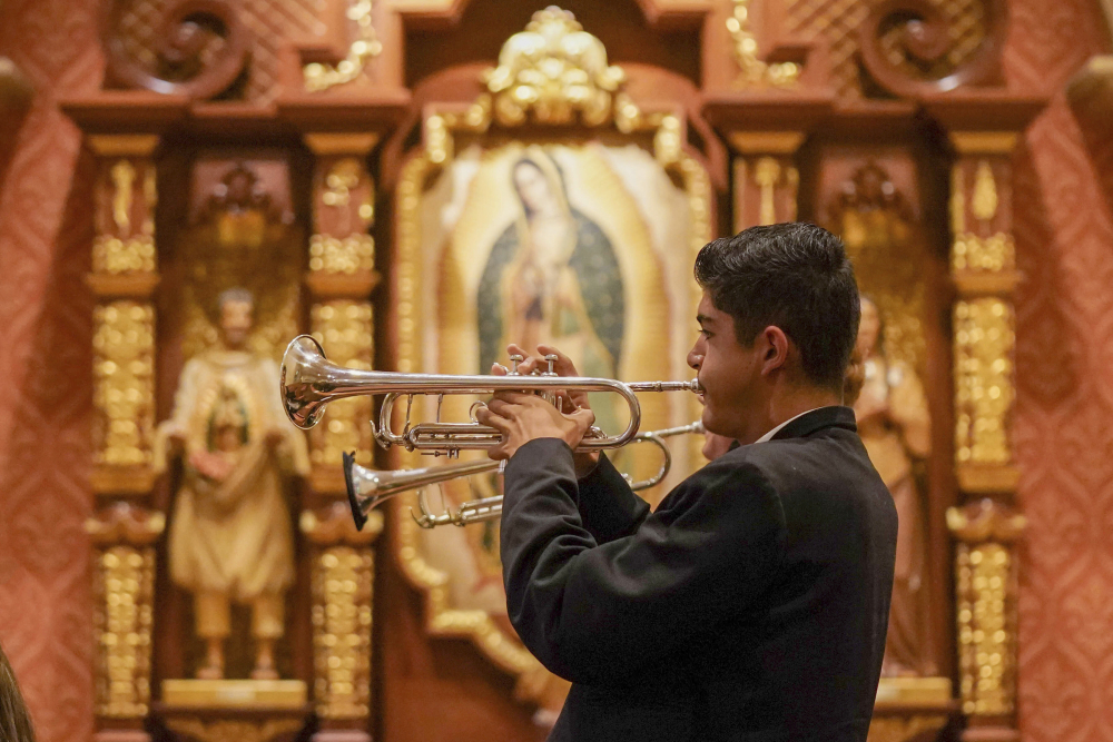 Los Changuitos Feos (Ugly Little Monkeys) mariachi band members Roman Murillo, 14, and Cameron Davison, 18, play their trumpets as they perform during the morning Mass at St. Augustine Cathedral Sunday in downtown Tucson.