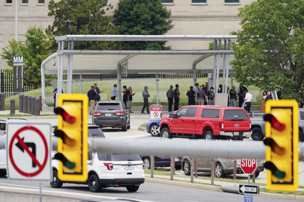 Police gather outside the Pentagon's Metro station Tuesday after the attack that left an officer and the suspect dead.