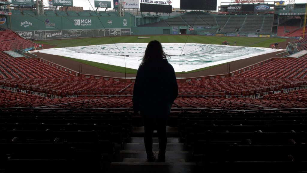 Emma Robertson stares out over Fenway Park in Boston during a rain delay at a recent Red Sox game. Robertson, a Mainer originally from South China, designed the tarp used during rain delays.