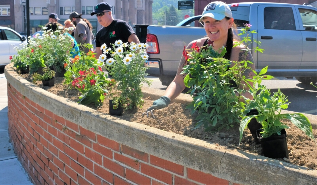 Stephanie Reed, the chair of Rumford's Beautify Rumford Committee, works with plants in one of the planters that she and committee members prepared for their town beautification project.
