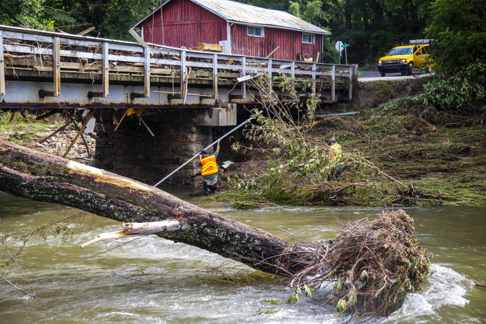 North Carolina highway workers assess damage to a bridge spanning the Pigeon River on Thursday in Bethel, N.C., after remnants from Tropical Storm Fred caused flooding in parts of western North Carolina on Tuesday. Search and rescue teams continue to search the area as 20 people are missing and 2 people were found dead.