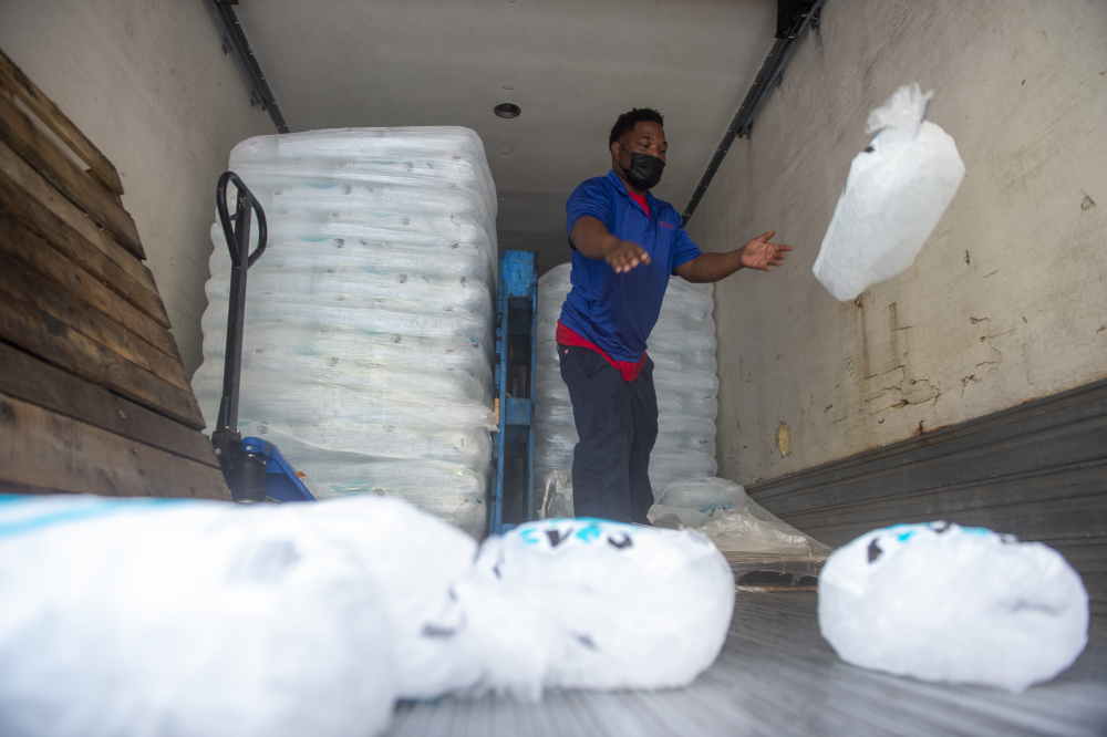 John Smith of Pelican Ice tosses bags of ice to the end of a truck as he helps stock a gas station in Jefferson, La., where residents were preparing for Hurricane Ida on Friday. Forecasters say Ida could be a major Category 3 hurricane with top winds of 115 mph when it nears the U.S. coast.