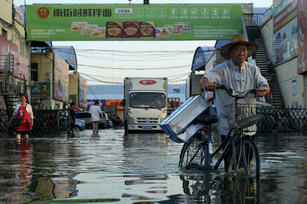 A man carries goods on his bicycle as he walks out of the the Yubei Agricultural and Aquatic Products World in Xinxiang in central China's Henan Province in July. The Intergovernmental Panel on Climate Change report released on Monday, Aug. 9, says warming already is smacking Earth hard and quickly with accelerating sea level rise, shrinking ice and worsening extremes such as heat waves, droughts, floods and storms.
