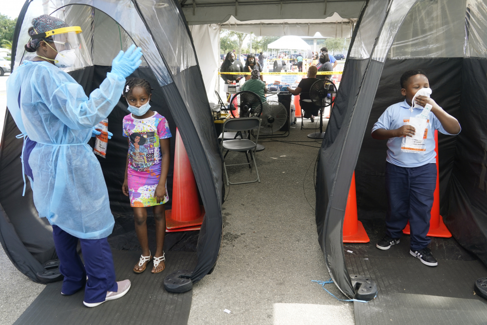 Wenderson Cerisene, 7, right, and his sister Dorah, 9, wait to get tested for COVID-19 on Tuesday in North Miami, Fla. The state has seen a dip in COVID-19 admissions in recent days.