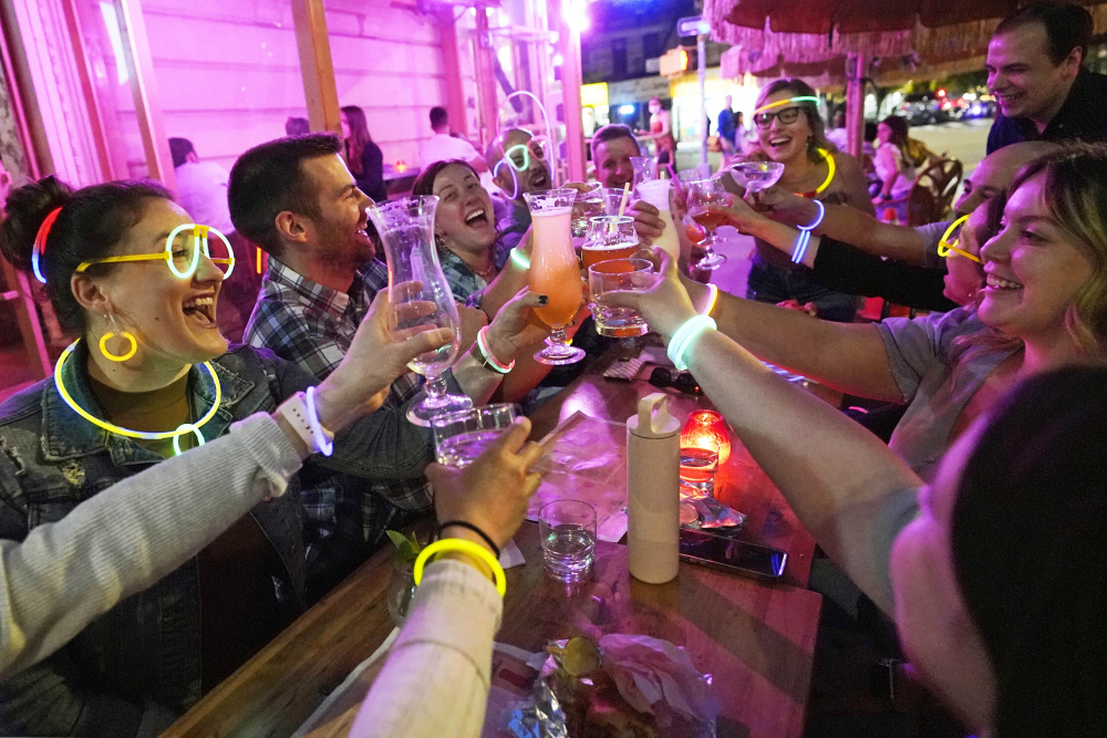 """Emily Baumgartner, left, and Luke Finley, second from left, join friends from their church group in a birthday toast to one of the members, upper right, during their weekly """"Monday Night Hang"""" gathering at the Tiki Bar on Manhattan's Upper West Side in May."""