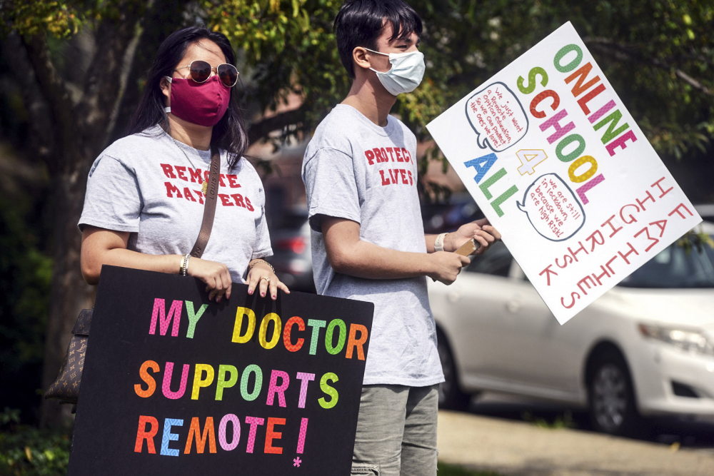 Macy Schulman, left, and Mason Yeoh, both students at Fairfield Warde High School, carry pro-remote learning signs during a rally of parents and students fighting to have an online option for school this year, Monday in Fairfield, Conn.