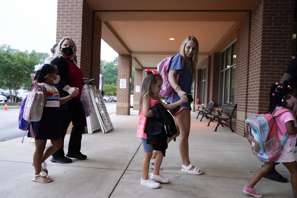 Students and parents walk to class at Tussahaw Elementary school on Wednesday  in McDonough, Ga.