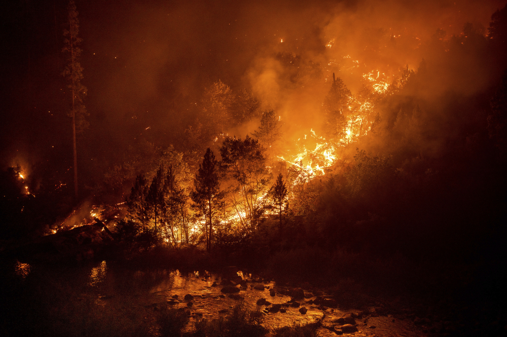 The Caldor Fire burns above the South Fork of the American River in the White Hall community of El Dorado County, Calif., on Friday.
