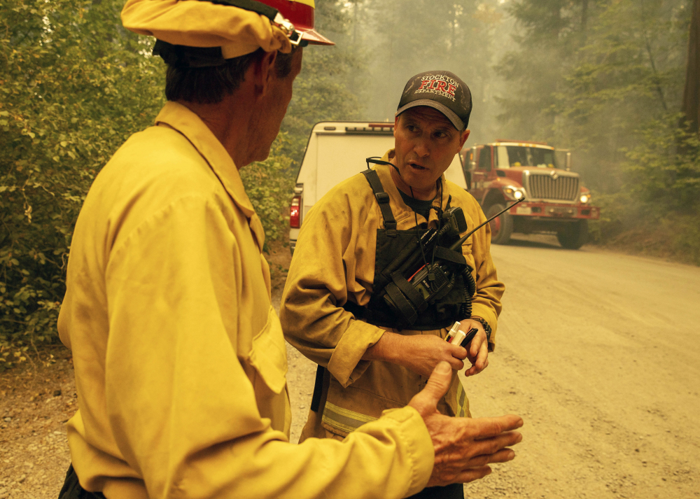 Firefighter Paul Schlange, left, confers while fighting the Caldor Fire  on Hazel Valley Road east of Riverton, Calif., on Thursday.