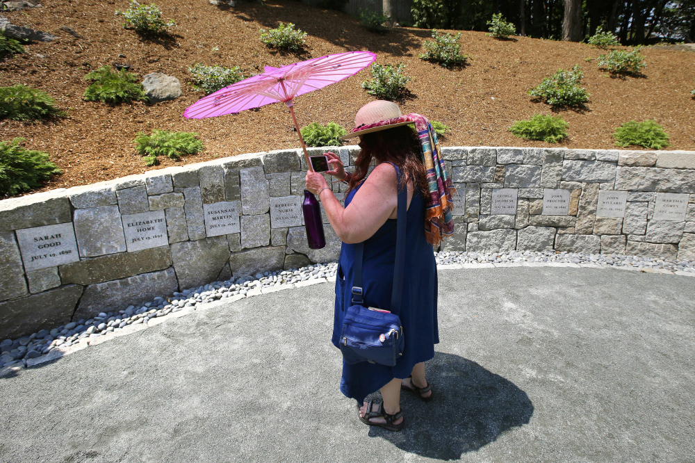 Karla Hailer, a fifth-grade teacher from Scituate, Mass., is shown in 2017 shooting a video where a memorial stands at the site in Salem, Mass., where five women were hanged as witches more than 325 years ago.