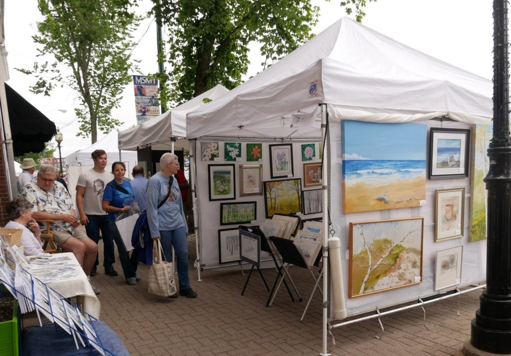 Visitors taking a look at paintings at the arts festival.